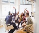 Excited creative business people giving high-five in meeting room at c